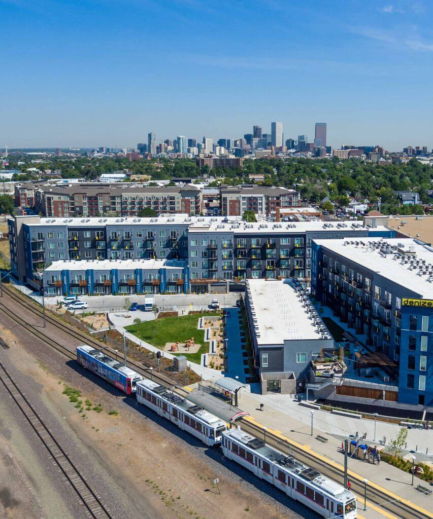 Exterior of Denizen Apartments including Light Rail and Denver Skyline